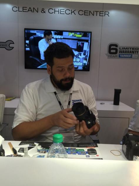 Riccardo Rizzo inspects and cleans my lens at the Tamron booth at the PhotoPlus Expo at the Jacob Javits Convention Center in New York on October 23, 2015. Photo by Lia Chang