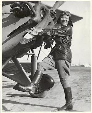 Katherine Sui Fun Cheung in pilots gear kickstarting propeller c1930's. Photo courtesy of Dottie